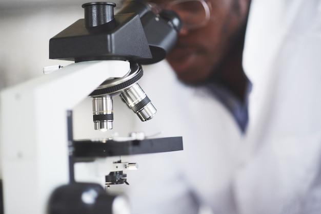 De wetenschapper werkt met een microscoop in een laboratorium en voert experimenten en formules uit. Gratis Foto