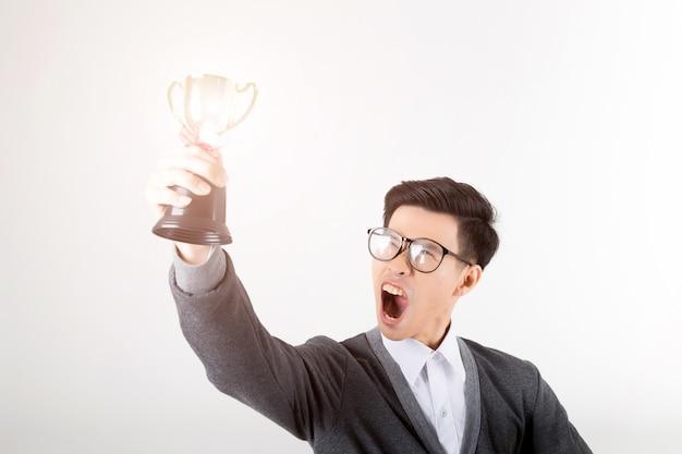 De winnaar die gouden trofee houdt. studio die op witte achtergrond is ontsproten. Premium Foto