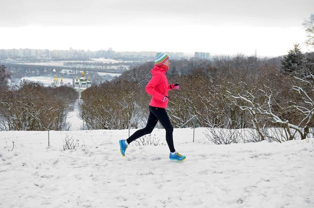 De winter die in park loopt: gelukkige actieve vrouwenagent die in sneeuw met kyiv-de horizonmening van de stadshorizon, openluchtsport en fitness concept aanstoot Premium Foto