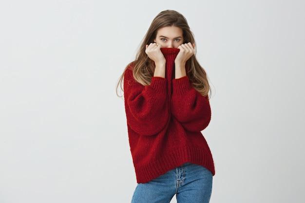 De winter is nabij. knappe slanke vrouw in trendy losse trui die haar gezicht in de kraag verbergt terwijl ze kijkt, het koud heeft of bloost van complimenten, staat. Gratis Foto
