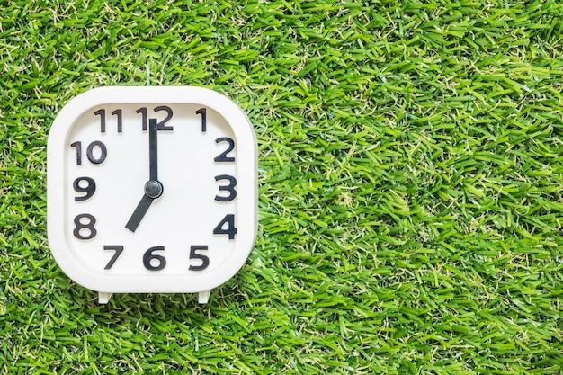 De witte klok van de close-up voor verfraait in 7 uur op groene kunstmatige grasvloer Premium Foto