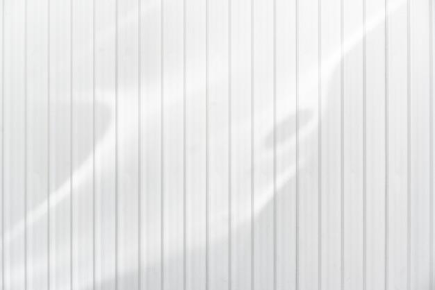De witte textuur van de golfmetaalmuur met samenvatting weerspiegeld zonlicht. horizontale achtergrondstructuur. Premium Foto