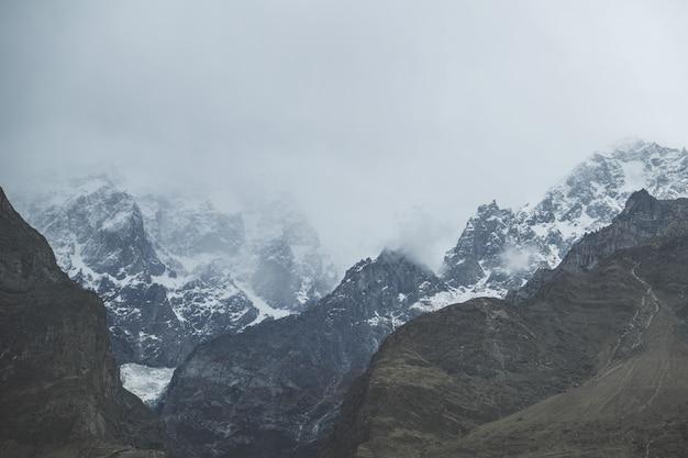 De wolken en de mist behandelden sneeuw afgedekte karakoram-bergketen, pakistan. Premium Foto