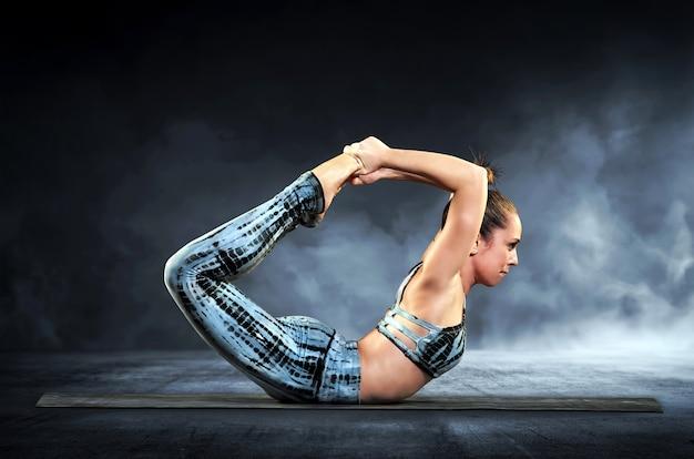 De yogavrouw die de boog aantonen stelt Premium Foto