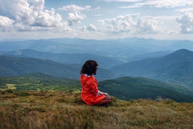 De yogavrouw zit in lotusbloem stelt op bergpiek. vrouw toeristische praktijken yoga en mediteert op de berg. rustend op de hoogste heuvel. Premium Foto