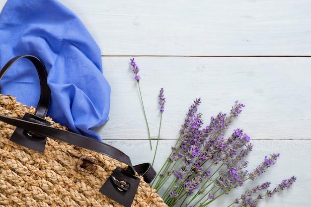 De zak van de vrouwenzomer met lavendelbloemen en blauwe sjaal op pastelkleur houten achtergrond Premium Foto