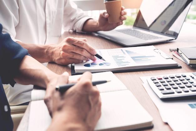 De zakenman bespreekt samen het verklaren van nieuwe tendenseninformatie over een document met collega-medewerker of partner in een modern bedrijfsbureau. Premium Foto
