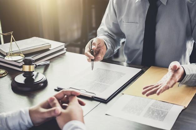 De zakenman en de mannelijke advocaat of de rechter raadplegen het hebben van teamvergadering met cliënt Premium Foto