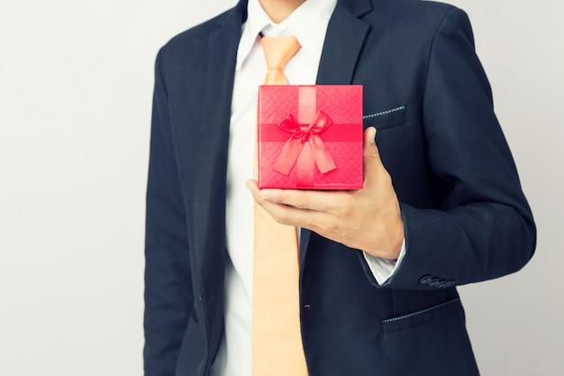 De zakenman houdt de gift rode doos, geïsoleerde achtergrond stand Premium Foto