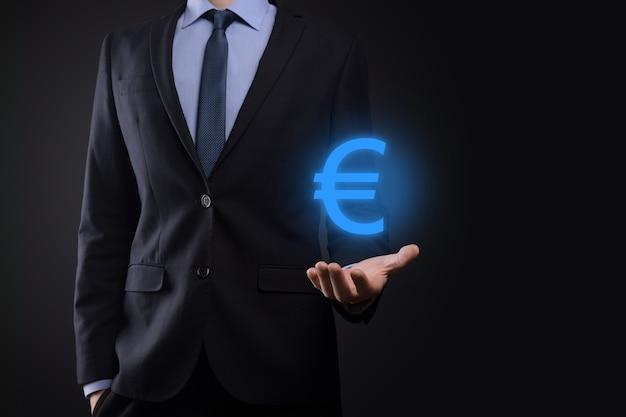 De zakenman houdt de pictogrammen van het geldmuntstuk eur of euro op donkere toonachtergrond. Premium Foto