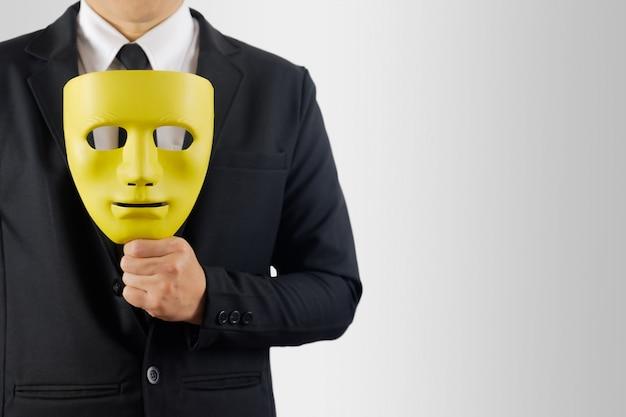 De zakenman houdt het masker in hand op grijs Premium Foto
