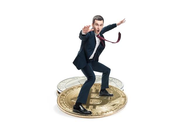 De zakenman in pak die zich op groot bedrijfspictogram bevindt. mannelijke figuur en litecoin geïsoleerd op een witte achtergrond. crypto-valuta, bitcoin, ethereum, e-commerce, financieel concept. collage Gratis Foto