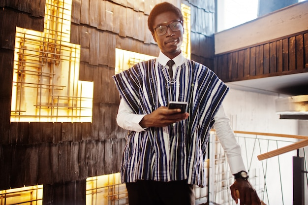 De zakenman in traditionele kleren en glazen met mobiele telefoon stelde dichtbij bij de moderne bouw binnen Premium Foto