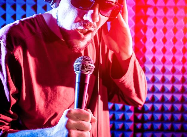 De zanger zingt met een microfoon in de opnamestudio. Premium Foto