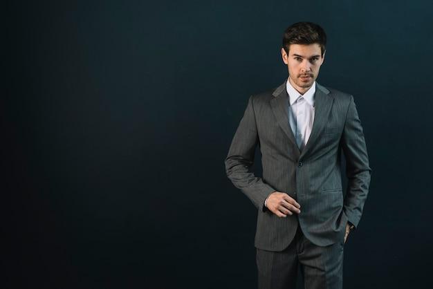 De zekere jonge mens met van hem dient zak tegen zwarte achtergrond in Gratis Foto
