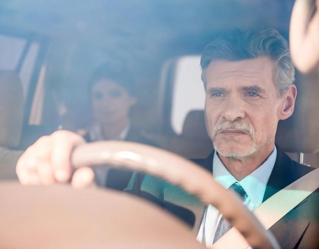 De zekere zakenman in kostuum drijft zijn luxueuze auto. Premium Foto