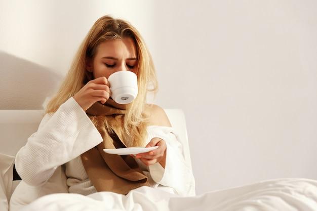 De zieke blonde vrouw ligt met een sjaal in het bed en drinkt hete thee Premium Foto