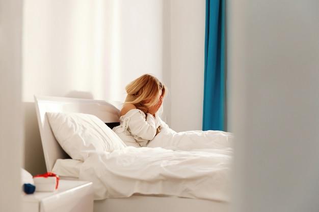 De zieke blonde vrouw ligt met een sjaal in het bed en niest Premium Foto