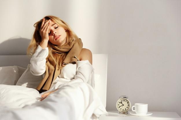 De zieke blonde vrouw ligt met een sjaal in het bed met hoofdpijn en koorts Premium Foto