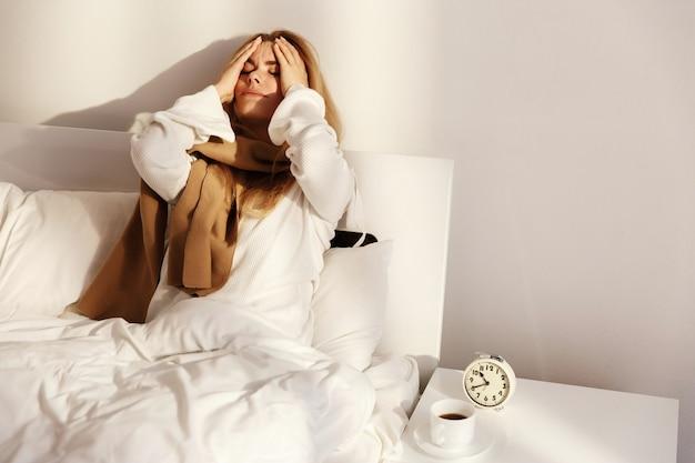 De zieke blonde vrouw ligt met een sjaal in het bed Premium Foto