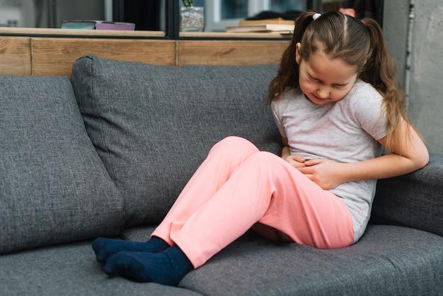 De zieke meisjeszitting op grijze bank lijdt aan maagpijn thuis Gratis Foto