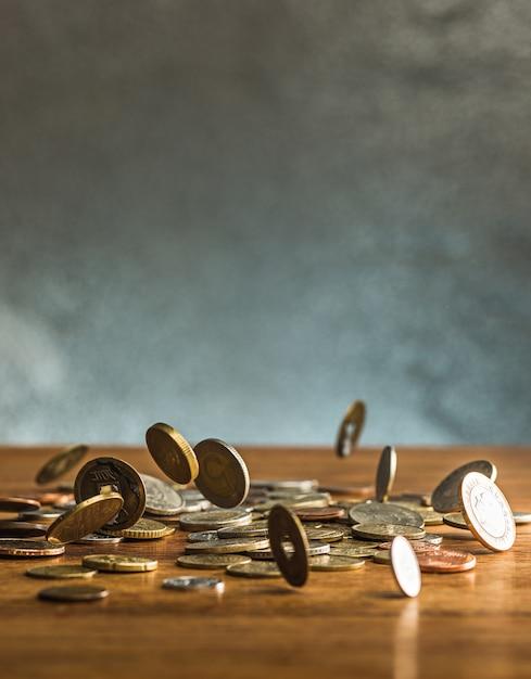 De zilveren en gouden munten en vallende munten op houten achtergrond Gratis Foto