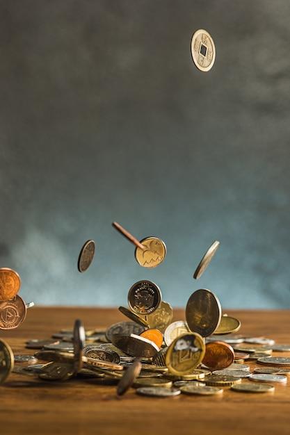De zilveren en gouden munten en vallende munten op houten muur Gratis Foto