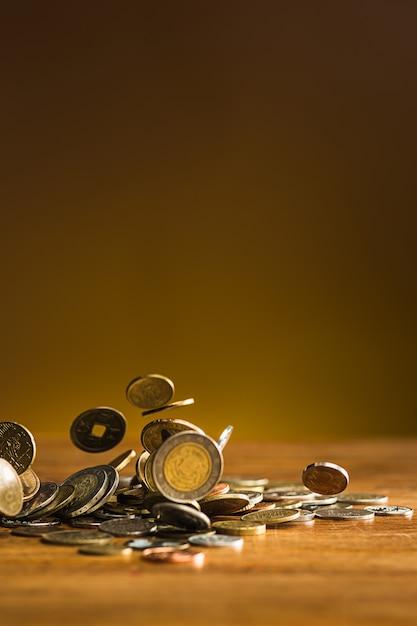 De zilveren en gouden munten en vallende munten op houten tafel Gratis Foto