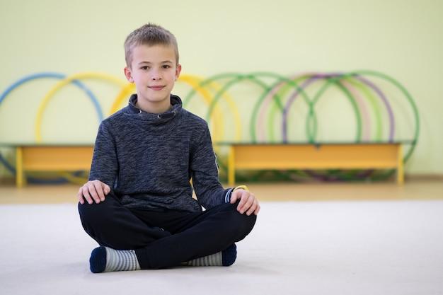 De zitting en de relaxiong van de jong kindjongen op de vloer binnen sportenruimte in een school na opleiding. Premium Foto