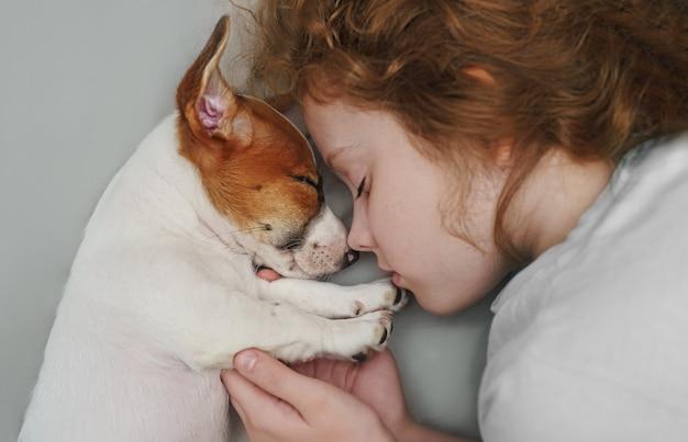 De zoete krullende meisje en puppyjasje russell hond slaapt in nacht. Premium Foto