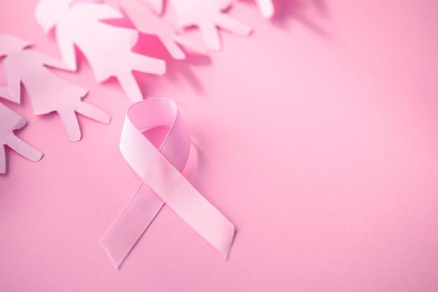 De zoete roze lintvorm met meisjesdocument pop op roze achtergrond voor de voorlichting van borstkanker Premium Foto