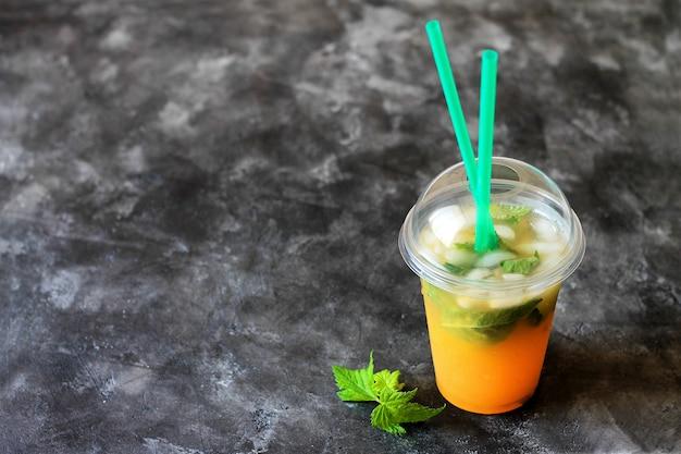De zomer drinkt limonade met sinaasappel en munt in de plastic kop op een donkere achtergrond. Premium Foto