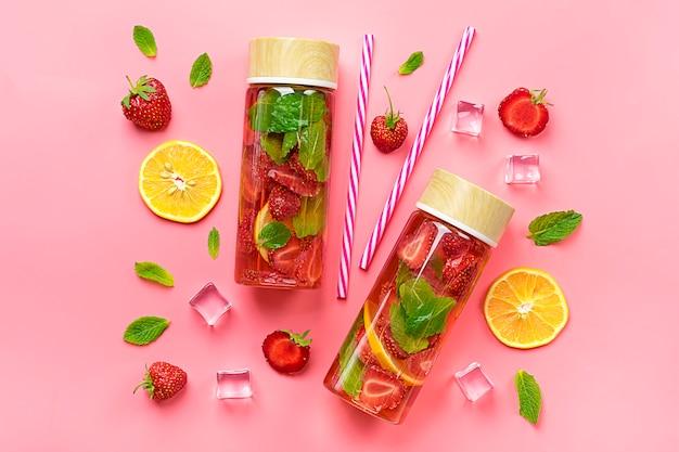 De zomerdrank met aardbei, citroen, blad van munt op roze achtergrond. Premium Foto