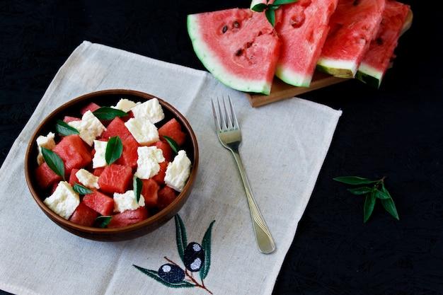 De zomersalade met watermeloen, witte kaas en basilicum in een kleiplaat op een zwarte achtergrond Premium Foto