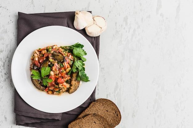 De zomersalade van aubergine en tomaat op een witte plaat Premium Foto