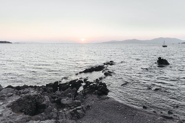 De zon gaat naar beneden over de zee en de zwarte rotsen ervoor Gratis Foto