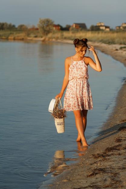 De zon schijnt op het model. meisje bij zonsondergang aan zee met een strozak en een hoed gaat op blote voeten. de achtergrond is wazig. Premium Foto