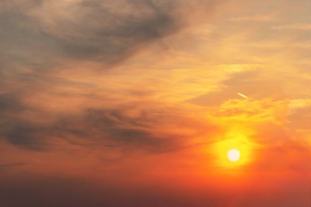 De zonsondergang aan de hemel is roodoranje en grijze wolken in de vorm van vlekken waarop de zon schijnt. Premium Foto