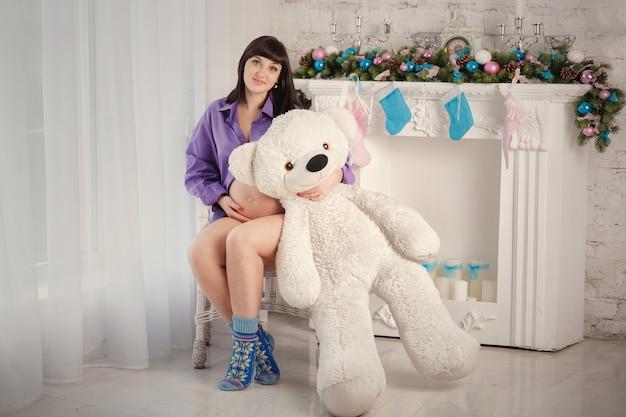 De zwangere vrouw met een polaire teddybeer zit bij een open haard Premium Foto