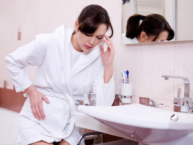 De zwangere vrouw met een sterke toxicose zit in de badkamer Gratis Foto