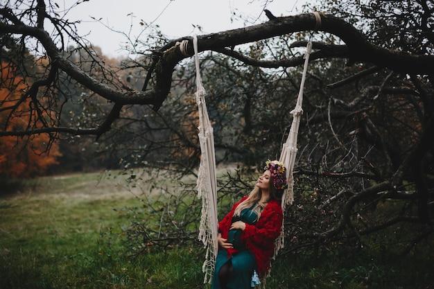 De zwangere vrouw rust buiten op de kabelschommeling hangend op oud rt Gratis Foto