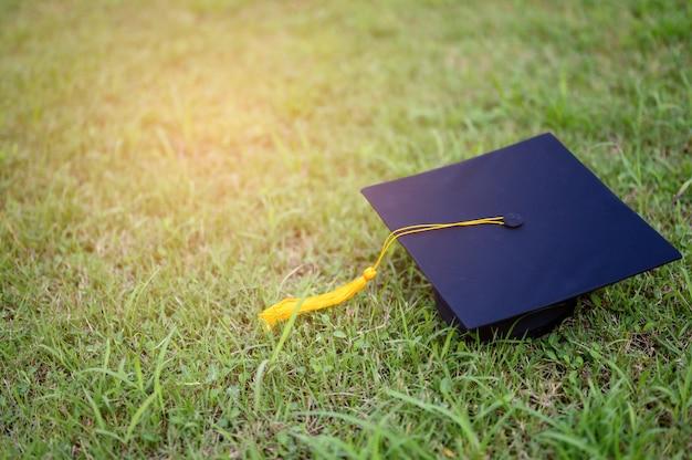 De zwarte hoed van universitair afgestudeerden staat op groene bladeren. Premium Foto