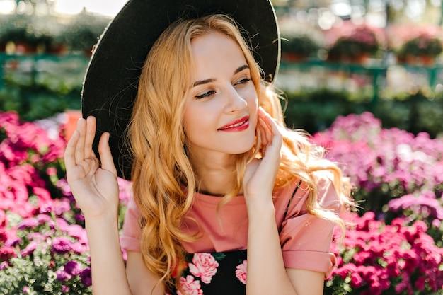 Debinair blanke vrouw poseren in frint van roze bloemen. nadenkend stijlvolle vrouw in hoed genieten van zomerdag. Gratis Foto