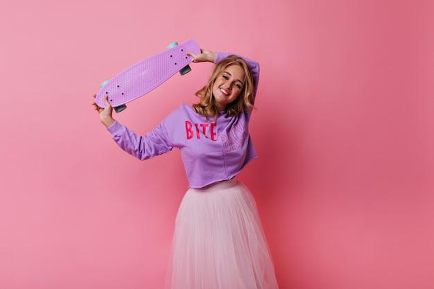 Debonair jongedame in weelderige rok chillen. sierlijke blonde meisje met roze skateboard. Gratis Foto