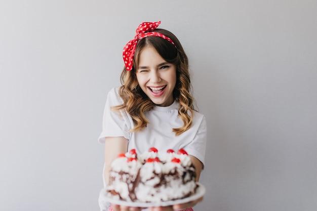Debonair meisje met romantische kapsel poseren met verjaardagstaart. geweldige lachende dame met aardbeientaart. Gratis Foto