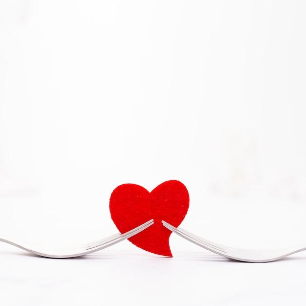 Decoratie met vorken die een rood hart houden Gratis Foto