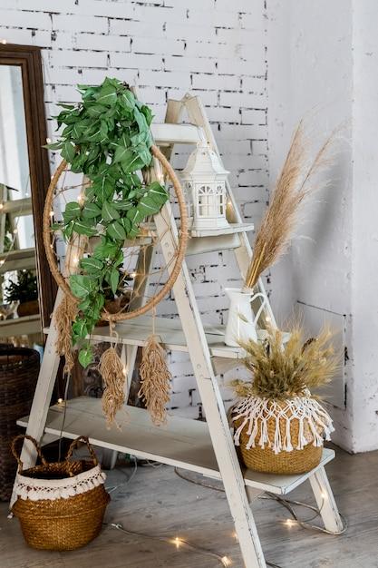 Decoratie voor gezellig huis gemaakt met droge kruiden, lantaarn, kaarsen en slingers op bakstenen muur. gedroogde bloemen en vegetatie in een modern interieur. interieur in eco-stijl Premium Foto