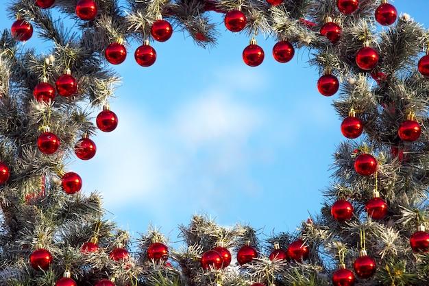 Decoratief frame van een versierde kerstboom op een azuurblauwe achtergrond Premium Foto