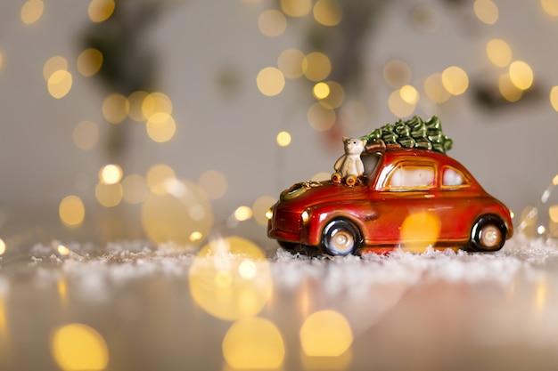 Decoratieve beeldjes van een kerstthema. een beeldje van een rode auto waarop een teddybeer zit. kerstboomdecoratie. feestelijk decor, warme bokehlichten. Premium Foto