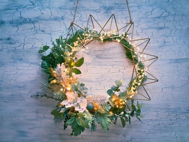 Decoratieve kerstkrans met spar, winterbladeren en bloemen op geometrisch gouden metalen frame met lichte slinger Premium Foto